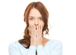 embarrassed woman covers mouth